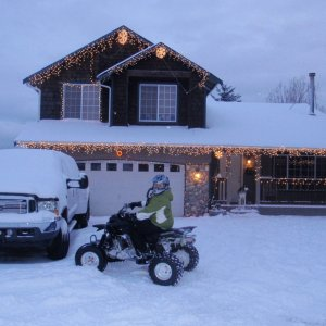 My wife on her quad by the dually in front of the house